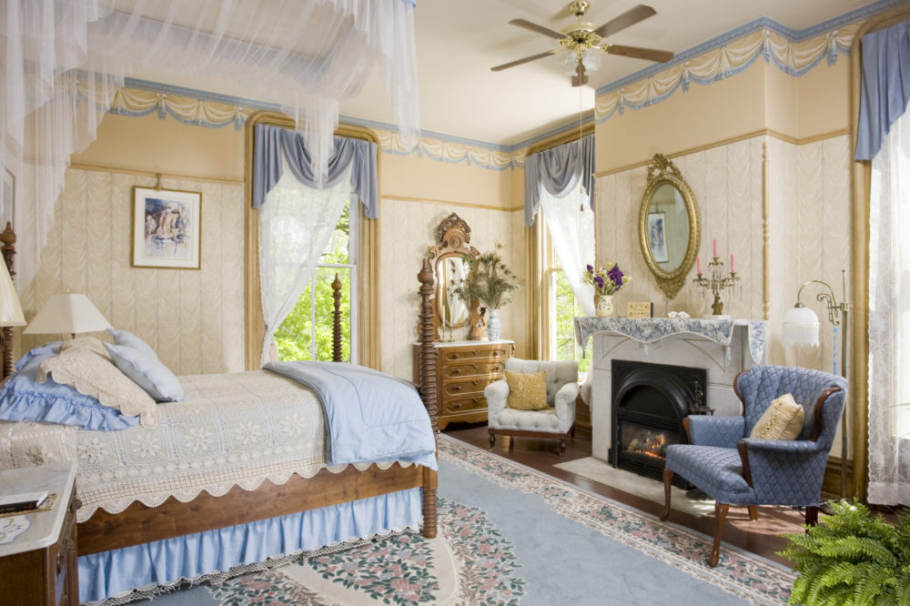 bedroom with canopy bed and chairs decorated in blue a bright light coming in from windows